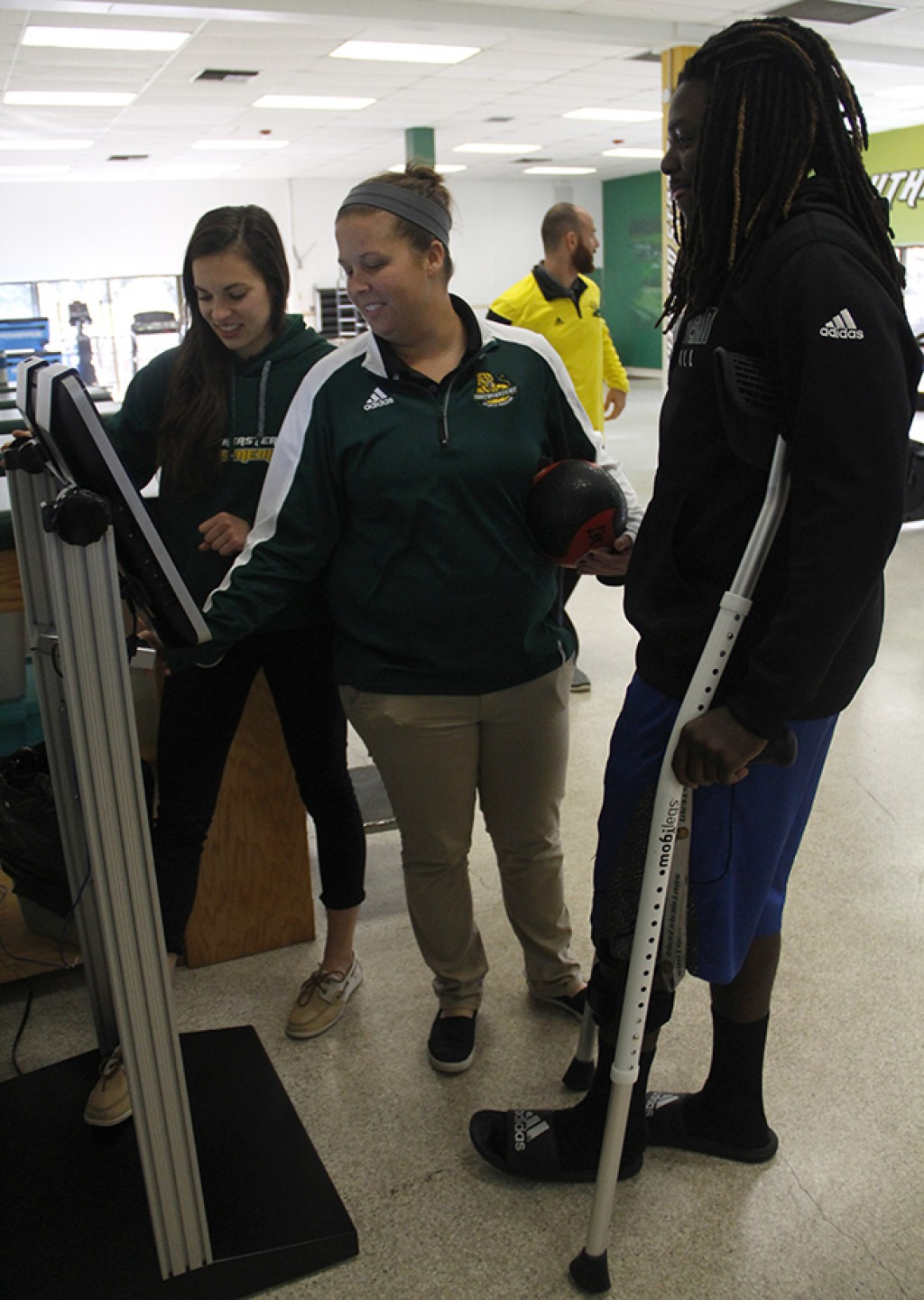 Jessica Van Sweden and Emily Gusew are assistant athletic trainers demonstrating how to use the login machine to athlete Tre' Bennett.