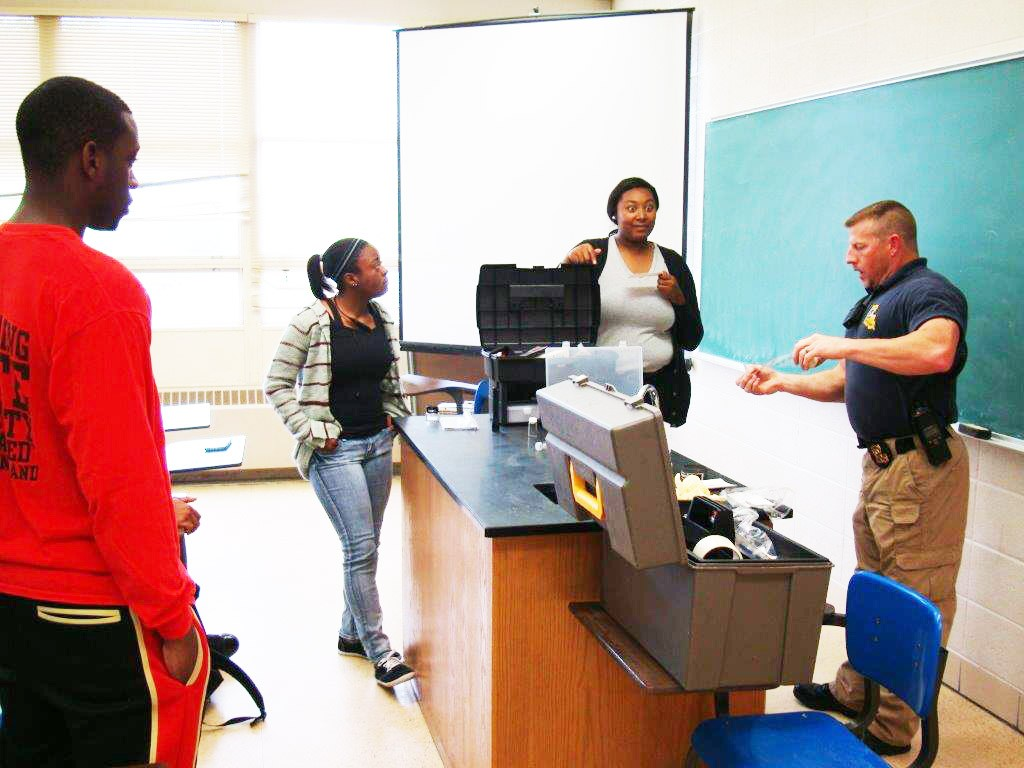 Courtesy photo Sgt. Rodney E. Pagans (right) explains some of the finer points of forensic chemistry to students  Daniel Jolla, Shermaine Shorter and Taiylor Watts.