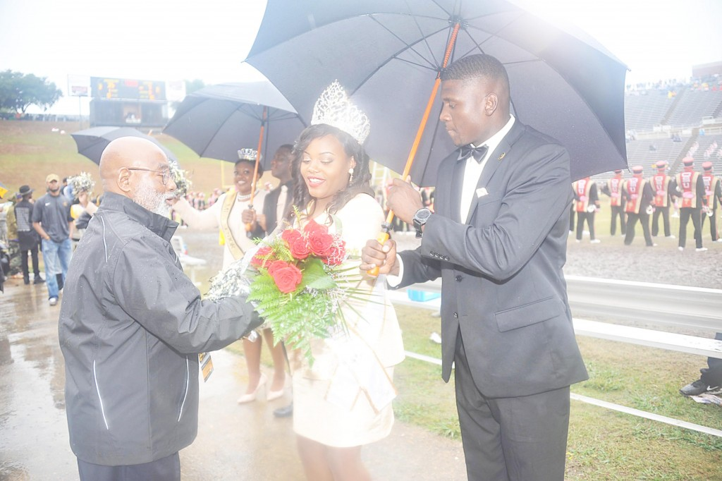 GLENN LEWIS/The Yearbook Miss GSU Joiya Smith receives flowers from President Willie Larkin as Desmond Stegall tries to hold the rain at bay.