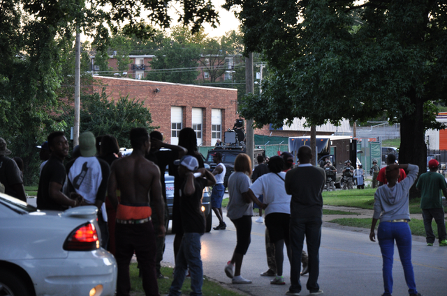 Protesters look on the SWAT barricade in Ferguson